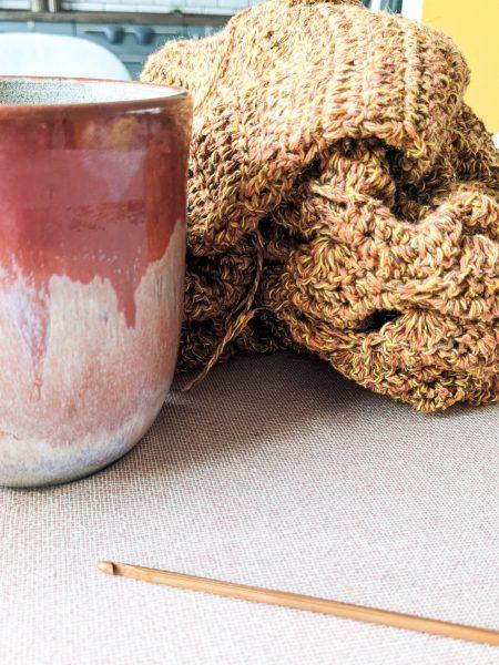 Thee, houten haaknaald en gehaakte sjaal